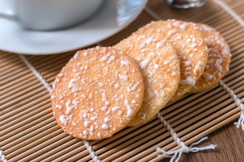Café sólo en la taza blanca y galletas curruscantes del arroz con en el woode foto de archivo libre de regalías