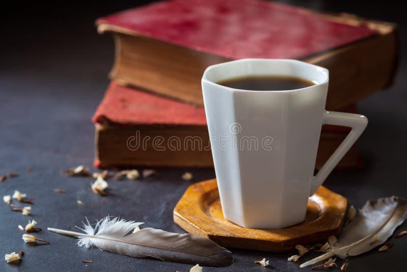 Café sólo en la taza blanca y libros viejos con la pluma y los pétalos secados de la flor imagen de archivo