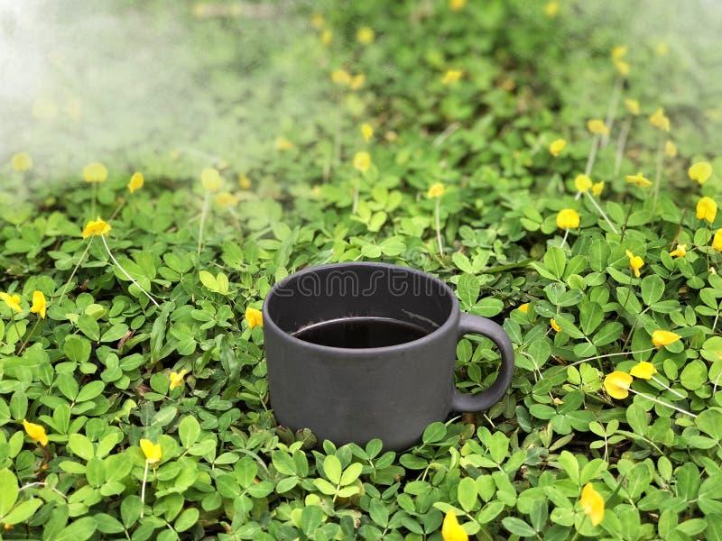 Café sólo en taza negra en la licencia verde y poco fondo amarillo de la flor imagen de archivo libre de regalías
