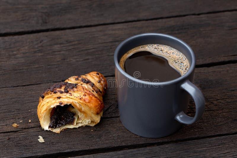 Café sólo en una taza de cerámica azul-gris al lado de una mitad del cruasán del chocolate aislada en la tabla de madera marrón o fotografía de archivo