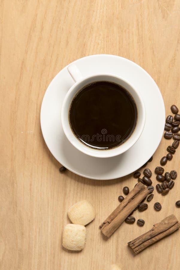 Café sólo en una taza y un platillo con granos de café, un palillo de canela y las galletas fotografía de archivo