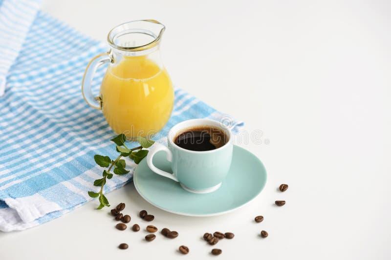Café sólo fuerte en una taza azul clara en una tabla blanca con el zumo de naranja fotos de archivo