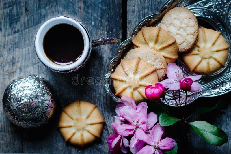 Café sabroso en una taza turca tradicional y galletas de mantequilla y una puntilla de flores rosadas en una tabla de madera - ba foto de archivo libre de regalías