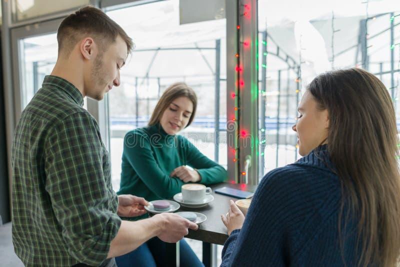 Café, saison d'hiver, deux jeunes femmes s'asseyant à la table avec la tasse de café, et barman masculin avec des macarons sur le photographie stock libre de droits