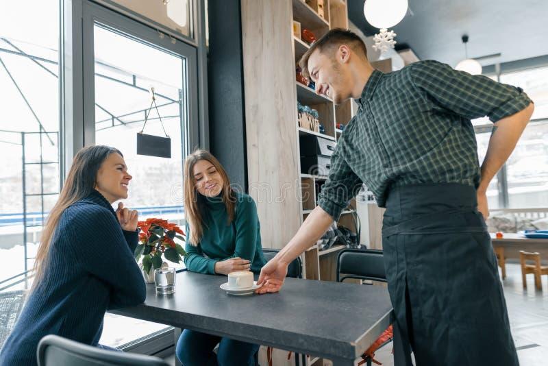 Café, saison d'hiver, deux jeunes femmes s'asseyant à la table, et un barman masculin avec une tasse de café souriant et parlant image stock