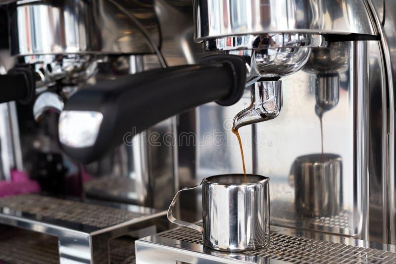 Café se renversant de machine d'expresso dans une petite cruche en métal photographie stock libre de droits