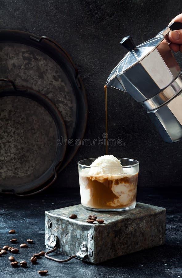Café se renversant de main femelle sur la glace à la vanille pour faire un café d'affogato Boisson de café d'été avec la crème gl photographie stock libre de droits