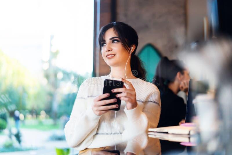 Café se reposant de jeune femme à la table, pensivement regardant la fenêtre, tenant le smartphone Fille de portrait avec le télé photographie stock