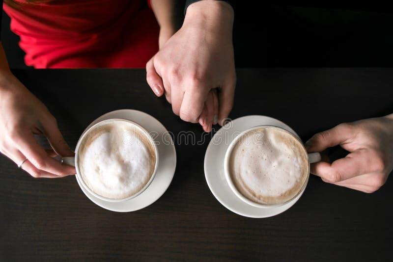 Café se reposant et potable de jeunes couples au restaurant de café deux tasses avec du café sont sur la table Mains de l'homme e image libre de droits
