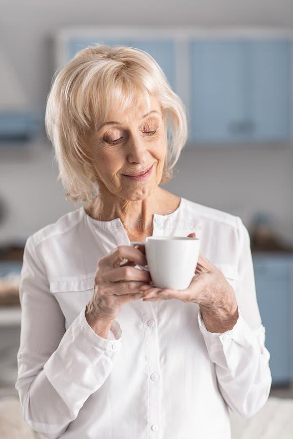 Café sentant de femme mûre avec du charme image stock