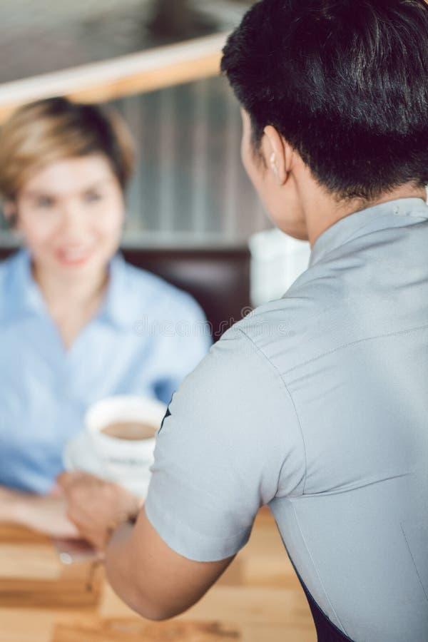 Café servant de serveur masculin au client féminin photographie stock libre de droits