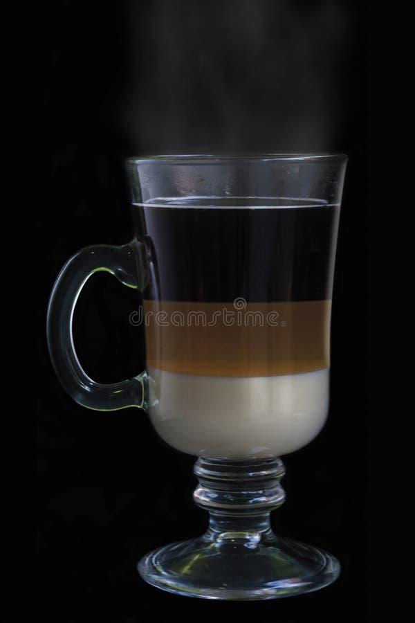 Café spécial dans une tasse en verre intéressante d'isolement sur le fond noir images stock