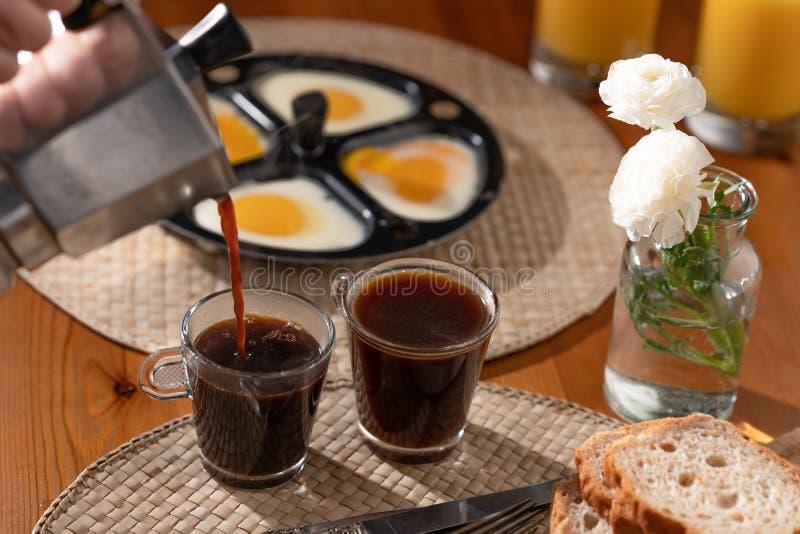 Café, suco de laranja, ovos em uma frigideira, e pão em uma mesa de cozinha, ainda vida do café da manhã, denominação da casa foto de stock royalty free