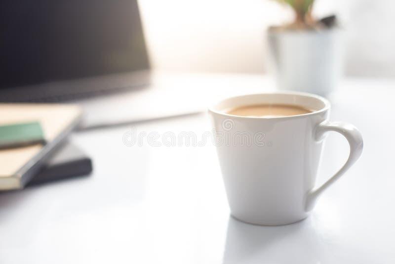 Café sur le carnet avec l'ordinateur portable sur la table blanche dans la lumière du soleil de matin, l'espace de fonctionnement photo stock