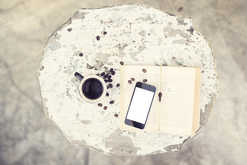 Café, téléphone portable vide et un livre sur la table image libre de droits