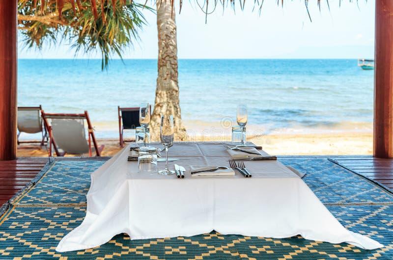 Café-Tabelle auf einem tropischen sandigen Strand mit Meer auf Hintergrund, Kanincheninsel, Kambodscha lizenzfreie stockbilder