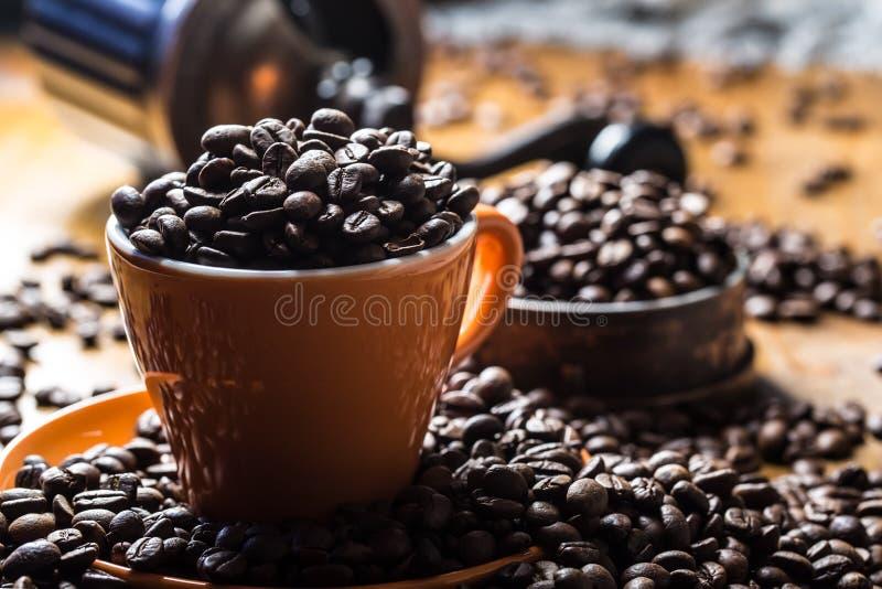 Café Taza de café por completo de los granos de café, amoladora de café en el fondo fotos de archivo