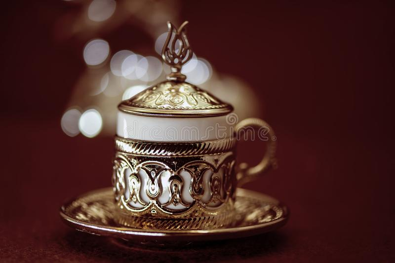 Café turc traditionnel dans la tasse traditionnelle en métal sur le fond brun avec le bokeh image stock