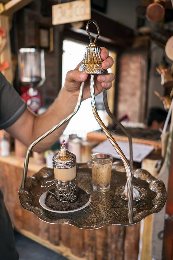 Café turc traditionnel servi dans la belle tasse en métal sur le sable chaud photo stock