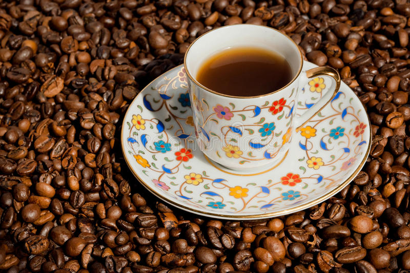 Café turco en pequeña taza con los modelos y los granos de café tradicionales fotografía de archivo libre de regalías