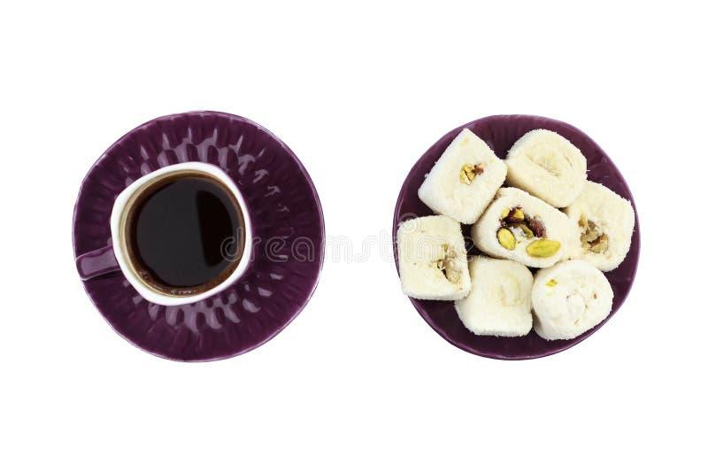 Café turco en taza púrpura y placer turco blanco con el pistacho y la nuez en la placa púrpura en fondo blanco aislado foto de archivo