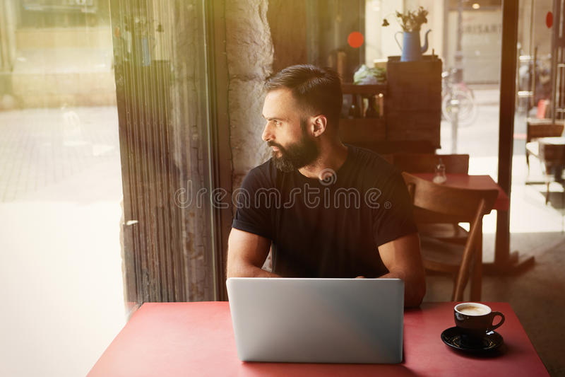 Café urbano de trabalho do portátil de Wearing Black Tshirt do homem de negócios farpado novo Vista de madeira de assento do café fotografia de stock royalty free