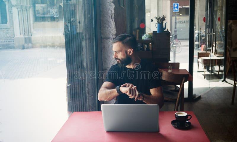 Café urbano de trabalho do portátil de Wearing Black Tshirt do homem de negócios farpado novo Vista de madeira de assento do café fotos de stock royalty free