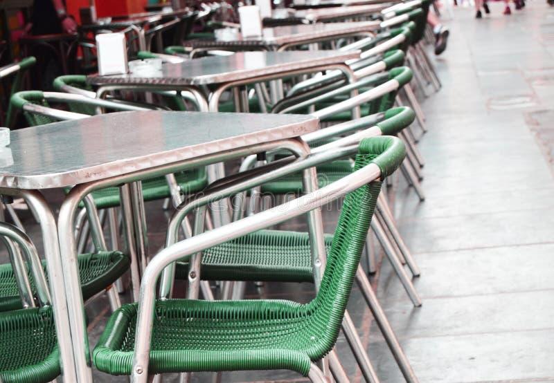 Café vacío abierto de la calle, tablas y sillas con el marco metálico y muebles de mimbre, foco selectivo y primer fotos de archivo