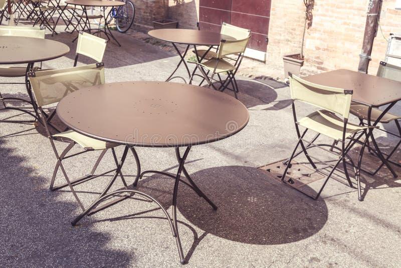 Café vazio da rua em Itália sob a luz solar Imagem tonificada foto de stock