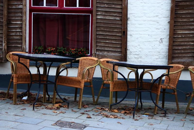 Café vazio da rua na cidade velha europeia Tabelas e cadeiras vazias contra a construção de tijolo branca velha com obturadores a fotos de stock