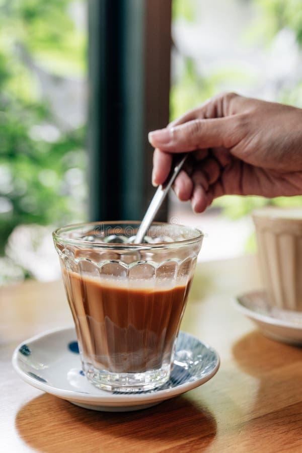 Café vietnamien servi chaud qui peut vous réveiller : La préparation de café noir avec condensent le lait en verre clair servi su photo stock