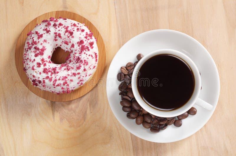 Café y buñuelo asperjado con el esmalte blanco fotos de archivo libres de regalías