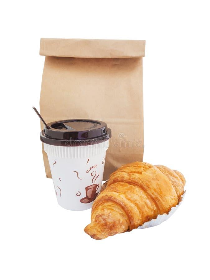 Café y cruasán con la bolsa de papel aislada imagen de archivo