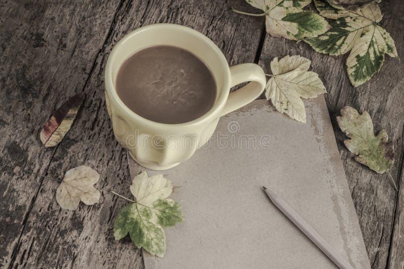 Café y cuaderno en la tabla de madera adornada con las hojas de otoño imágenes de archivo libres de regalías