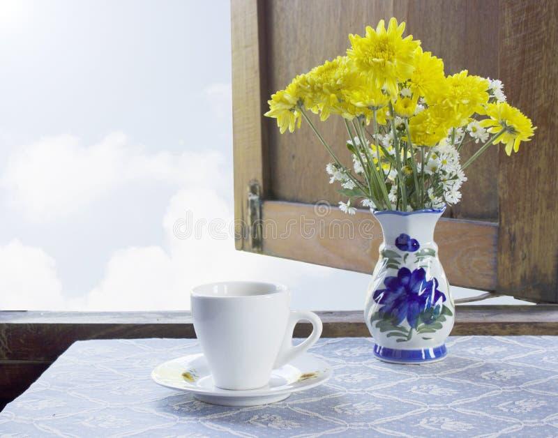 Café y flores en un florero foto de archivo