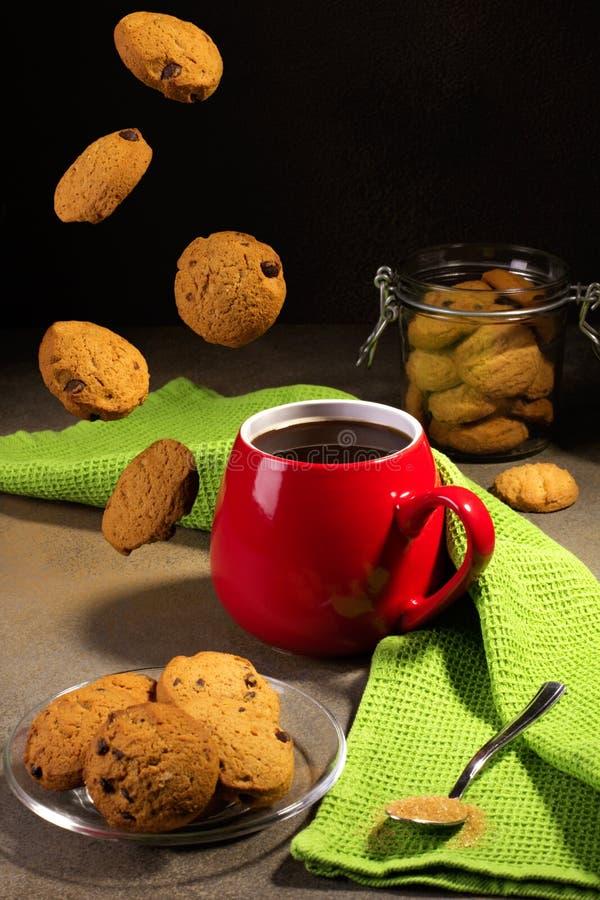 Café y galletas en fondo negro imagenes de archivo