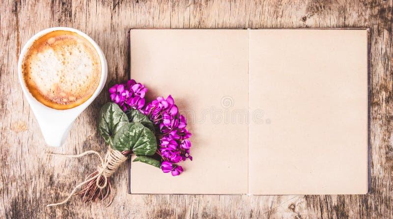Café y libro de la mañana taza de capuchino y de libro calientes abra el diario, el café y las flores vacíos fotos de archivo