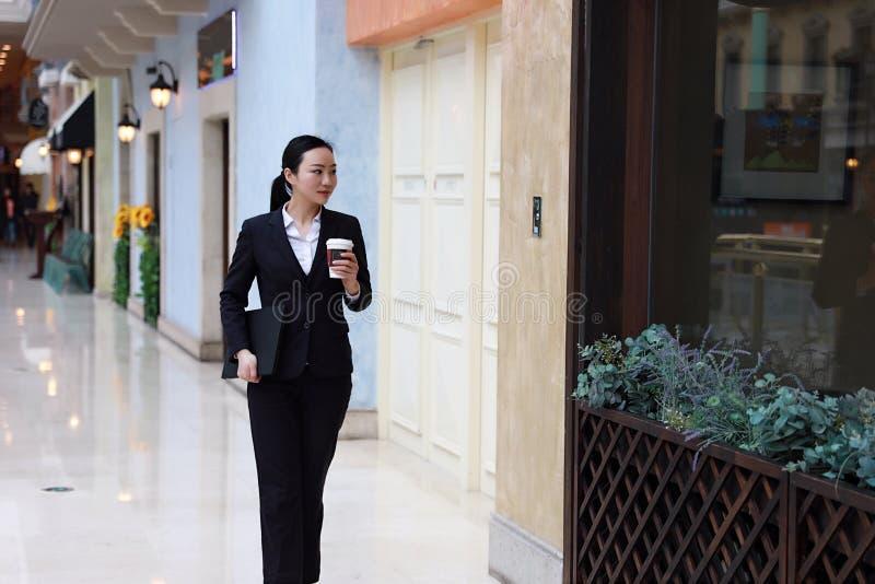 Café y ordenador portátil de consumición que caminan de la mujer de negocios en alameda de compras imagen de archivo libre de regalías