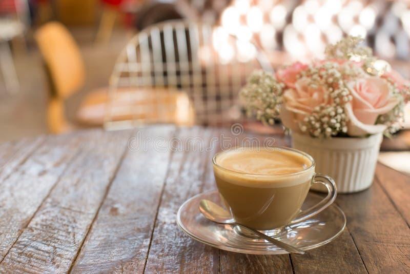café y ramo calientes de flor en la tabla de madera del grunge foto de archivo libre de regalías