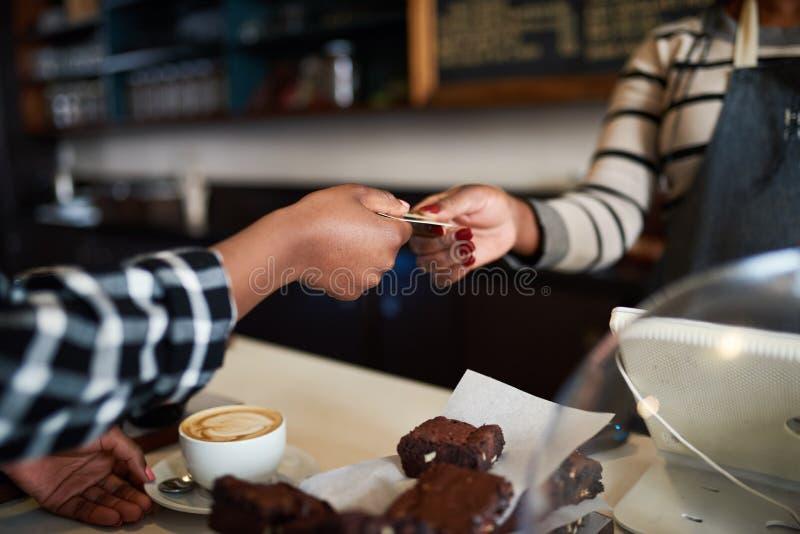 Cafékunde, der für eine Bestellung mit ihrer Kreditkarte zahlt stockfotos