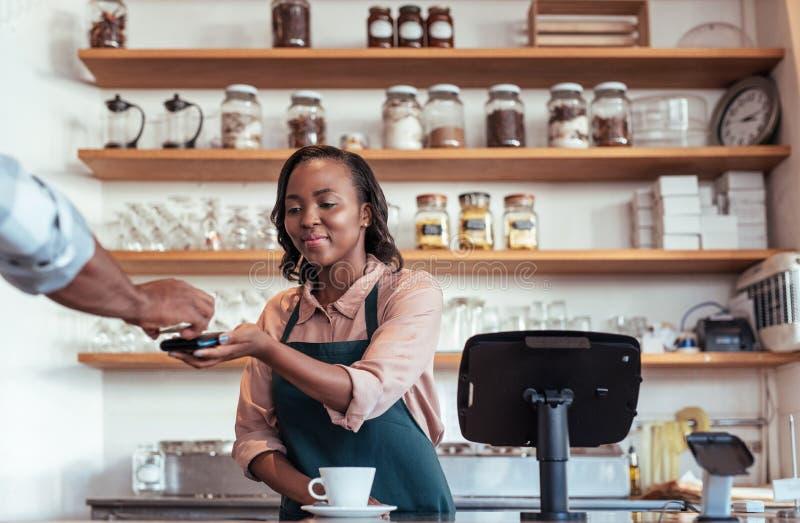 Cafékunde, der für ihr purchace mit nfc Technologie zahlt stockfotos