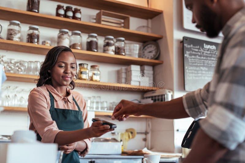 Cafékunde, der für sein purchace mit nfc Technologie zahlt stockfoto