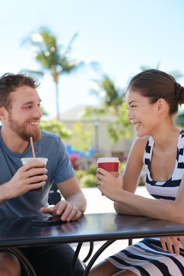 Cafépaare, welche die trinkende Kaffeeunterhaltung des Spaßes haben lizenzfreie stockfotos