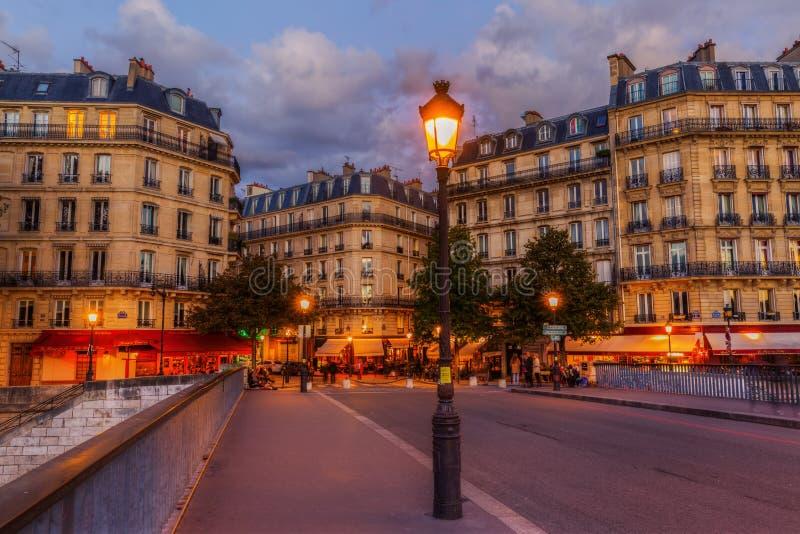Cafés de la calle en el Saint Louis de Ile en París en la noche imagenes de archivo