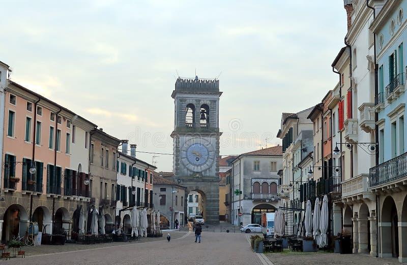 Cafés de la calle y puerta de la ciudad con la torre de reloj ornamental, Este, Véneto, Italia imagenes de archivo