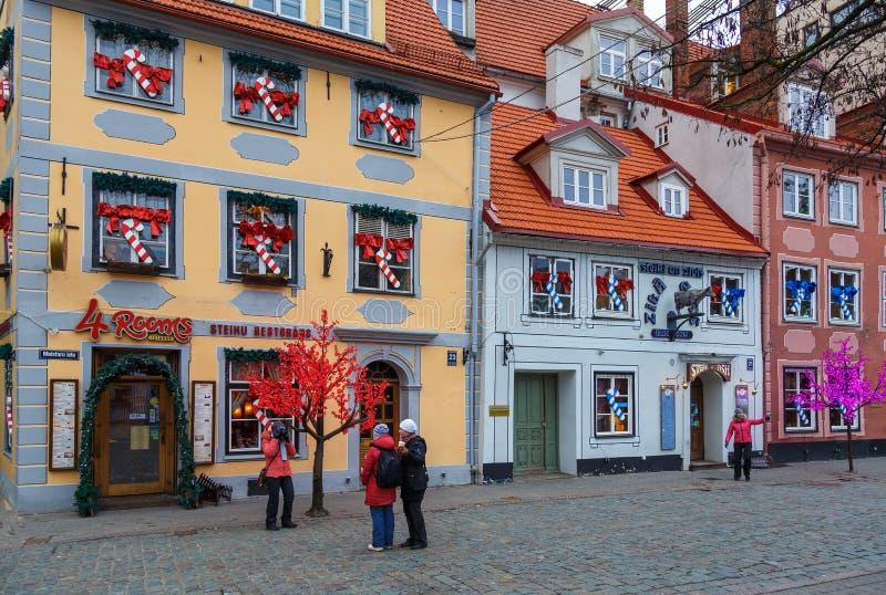 Cafés e restaurantes nas construções históricas da cidade velha do ` s de Riga foto de stock