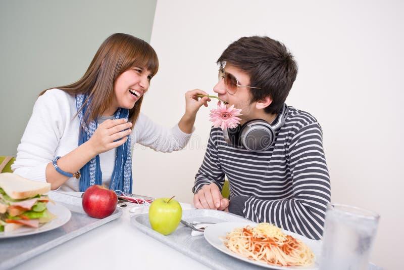 Cafétéria d'étudiant - couple d'adolescent ayant l'amusement images libres de droits