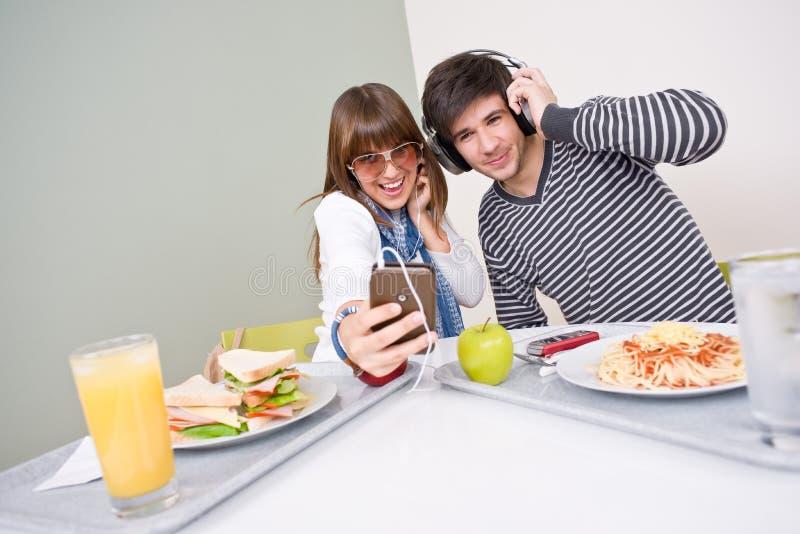 Cafétéria d'étudiant - couple d'adolescent ayant l'amusement photos stock