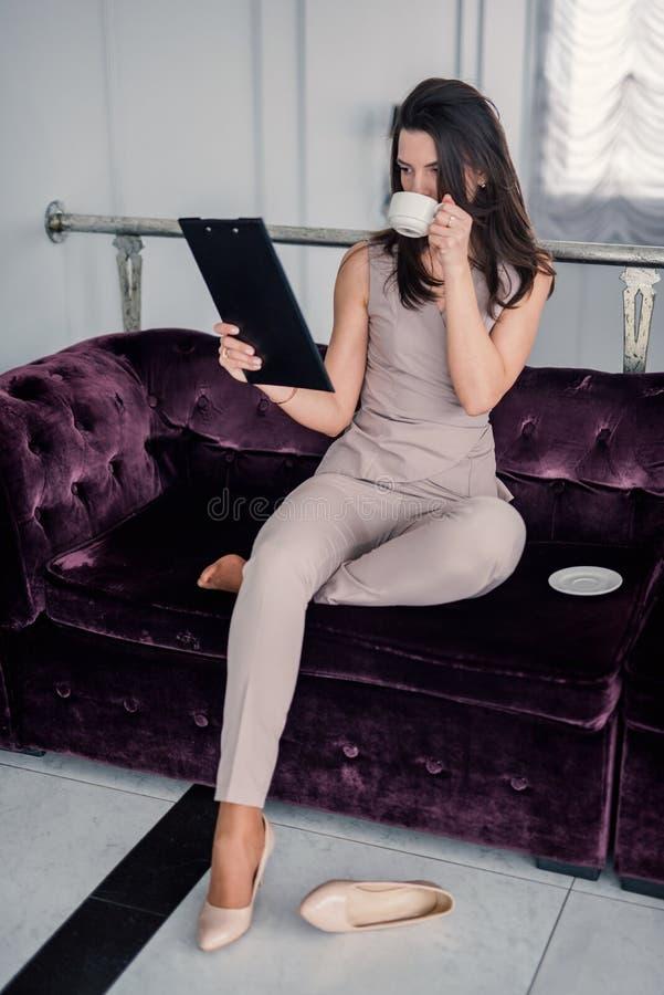 Caf? bebendo da mulher pensativa, usando o port?til e lendo originais em casa ao sentar-se no sof? Copie o espa?o imagem de stock