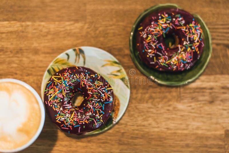 Caf? con un coraz?n y una leche exhaustos en una tabla de madera en una cafeter?a dos anillos de espuma del chocolate con la disp imagen de archivo